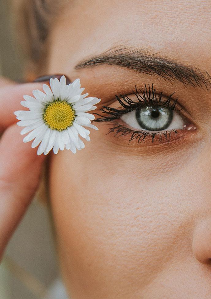 eyemed - Über uns, Frau mit Blume neben ihrem Auge