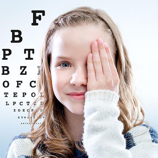 eyemed Berlin - Mädchen mit Hand vor einem Auge vor Buchstabentafel